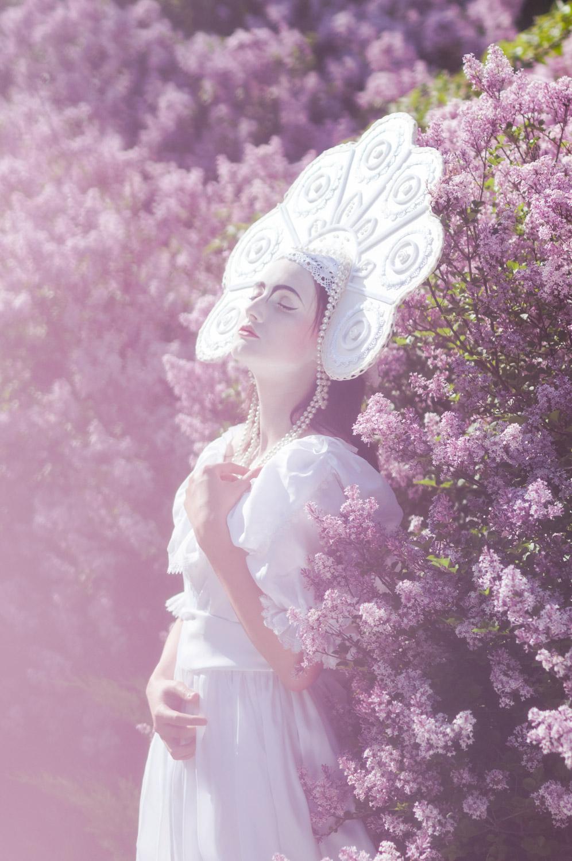 dziewczyna w białej sukni i kokoszniku na tle kwitnących krzewów