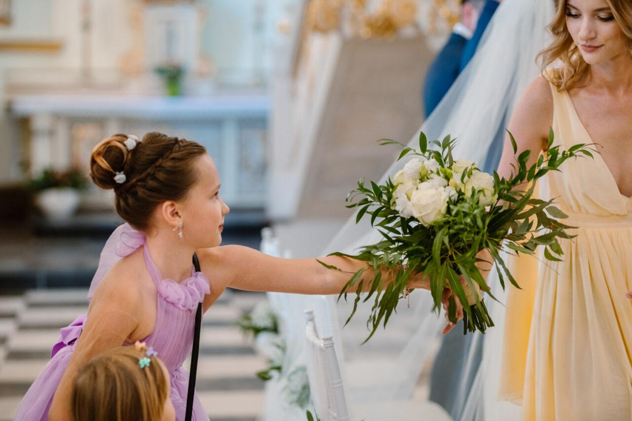 dziewczynka podaje druhnie bukiet ślubny