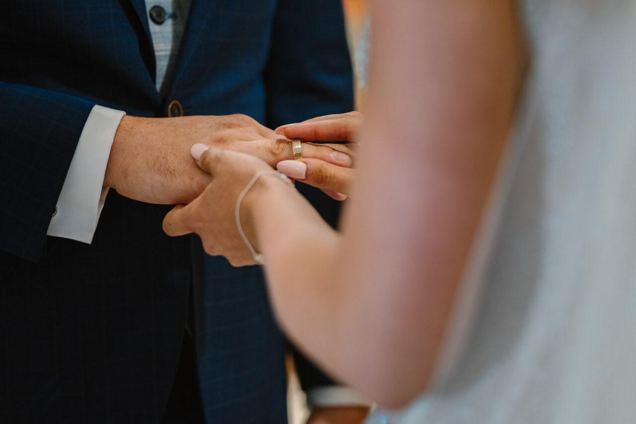 panna młoda zakłada obrączkę ślubną mężowi