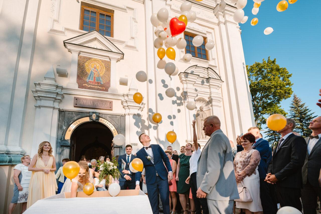 para młoda wypuszcza balony przed kościołem