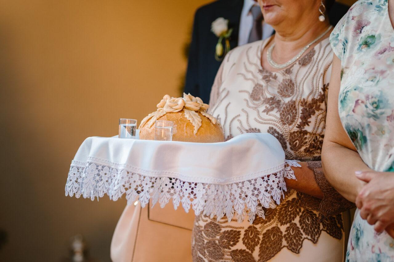 chleb z solą i kieliszki w rękach rodziców pary młodej