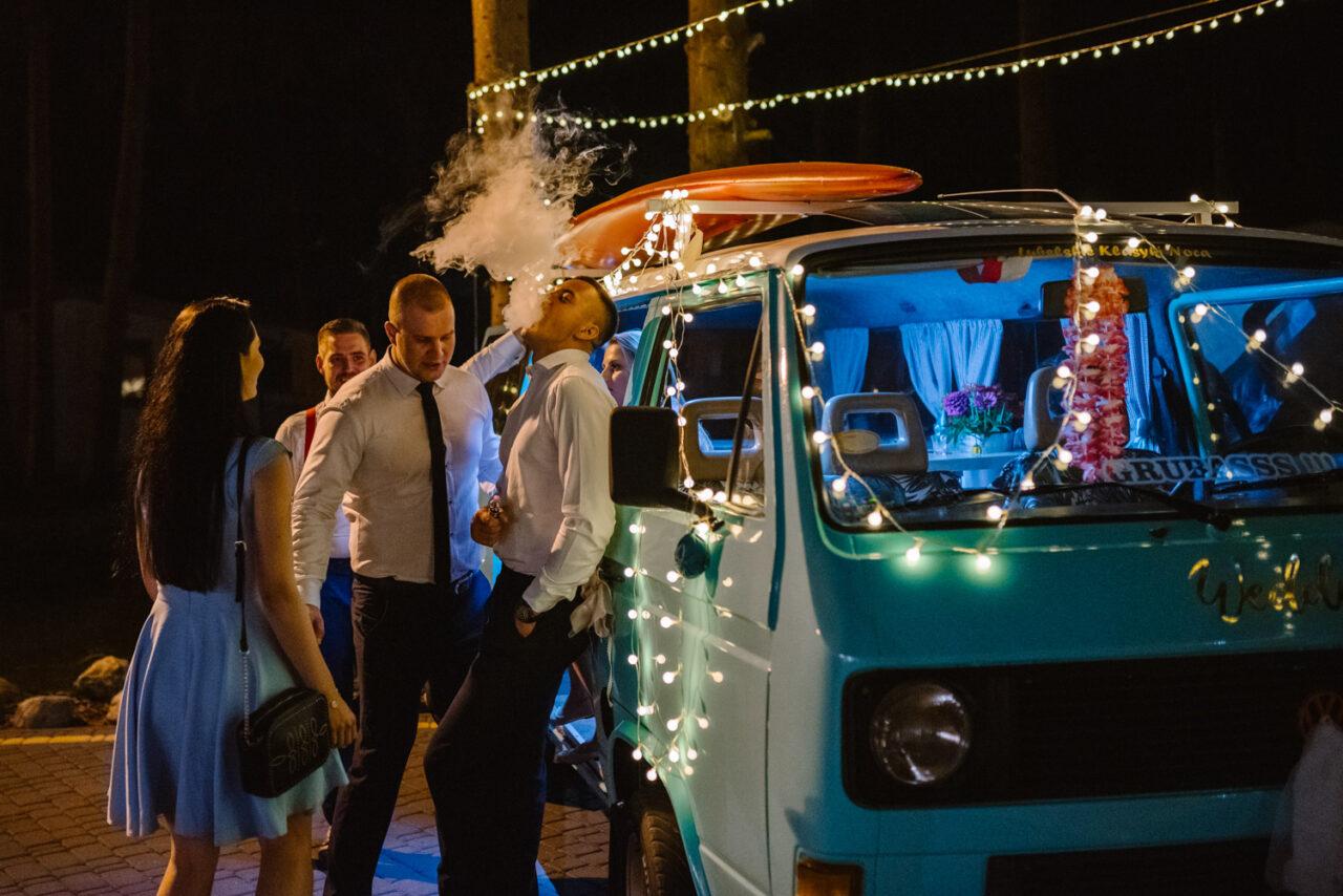 goście weselni palący papierosy przy aucie nocą