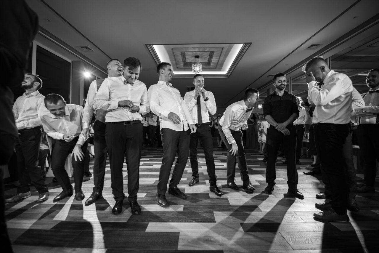 mężczyźni bawiący się na weselu