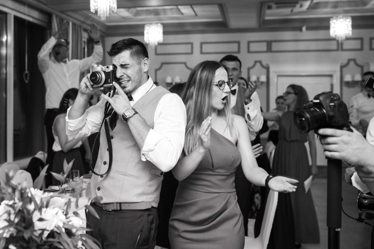 goście weselni i chłopak z aparatem
