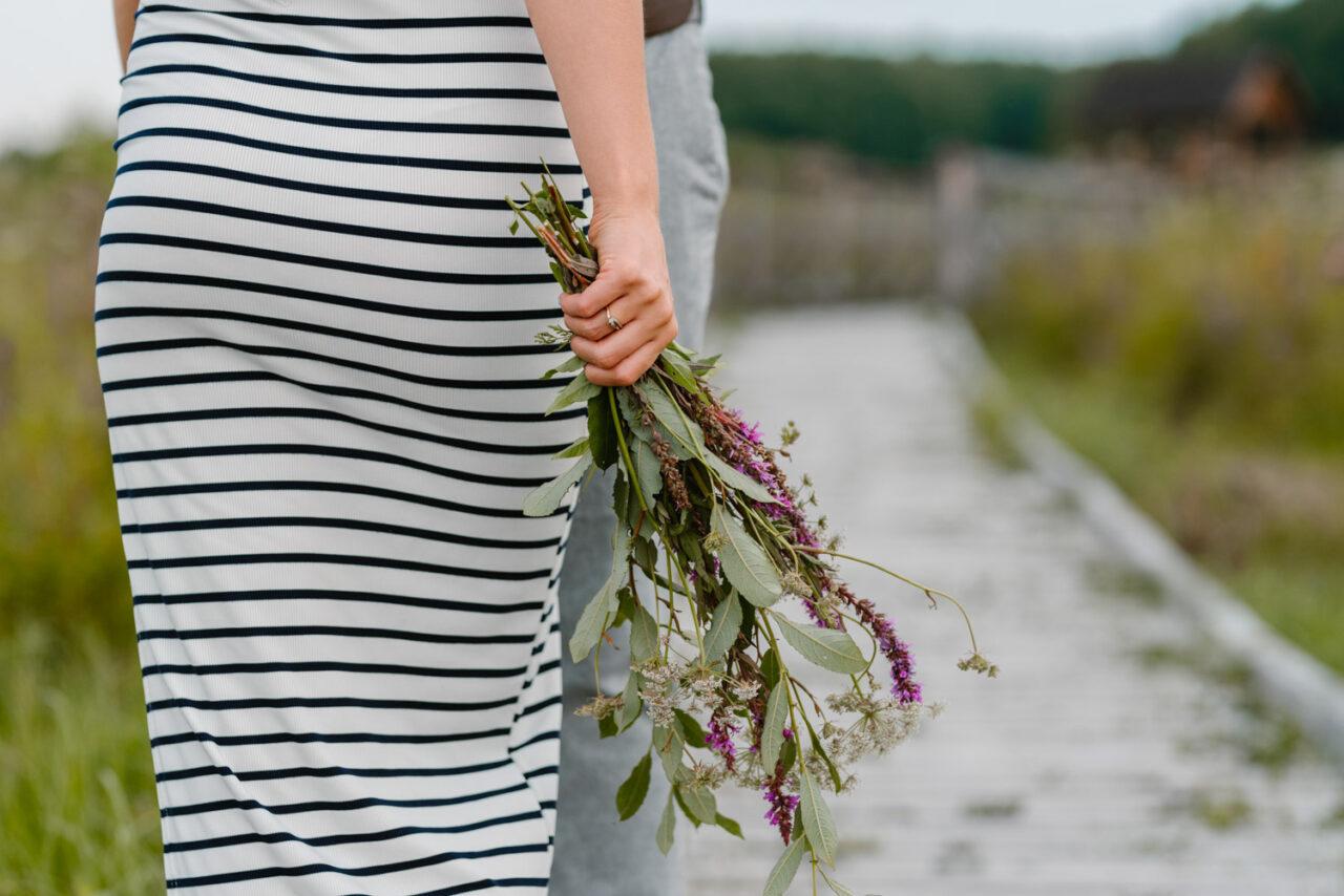 kobieca dłoń trzymająca bukiet polnych kwiatów