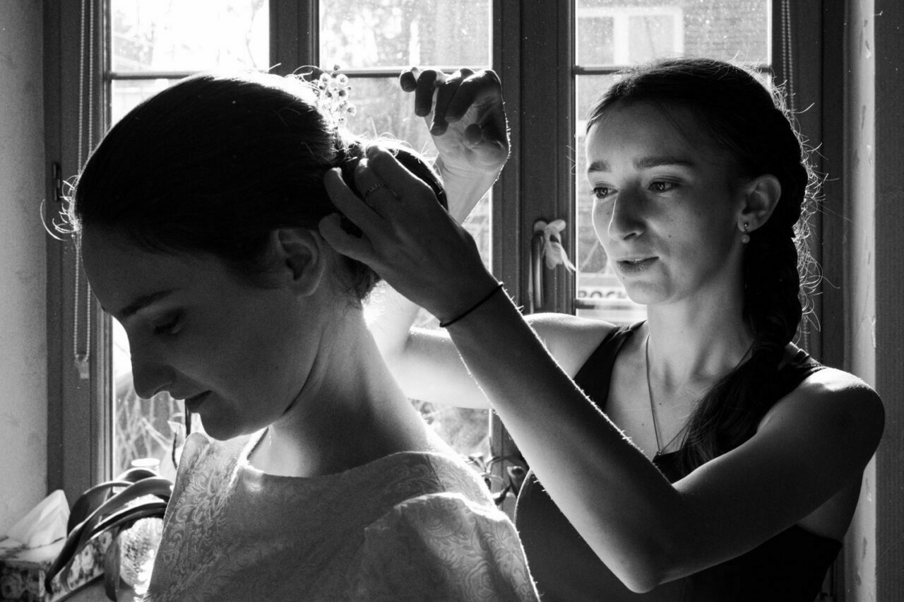 druhna poprawia fryzurę pannie młodej