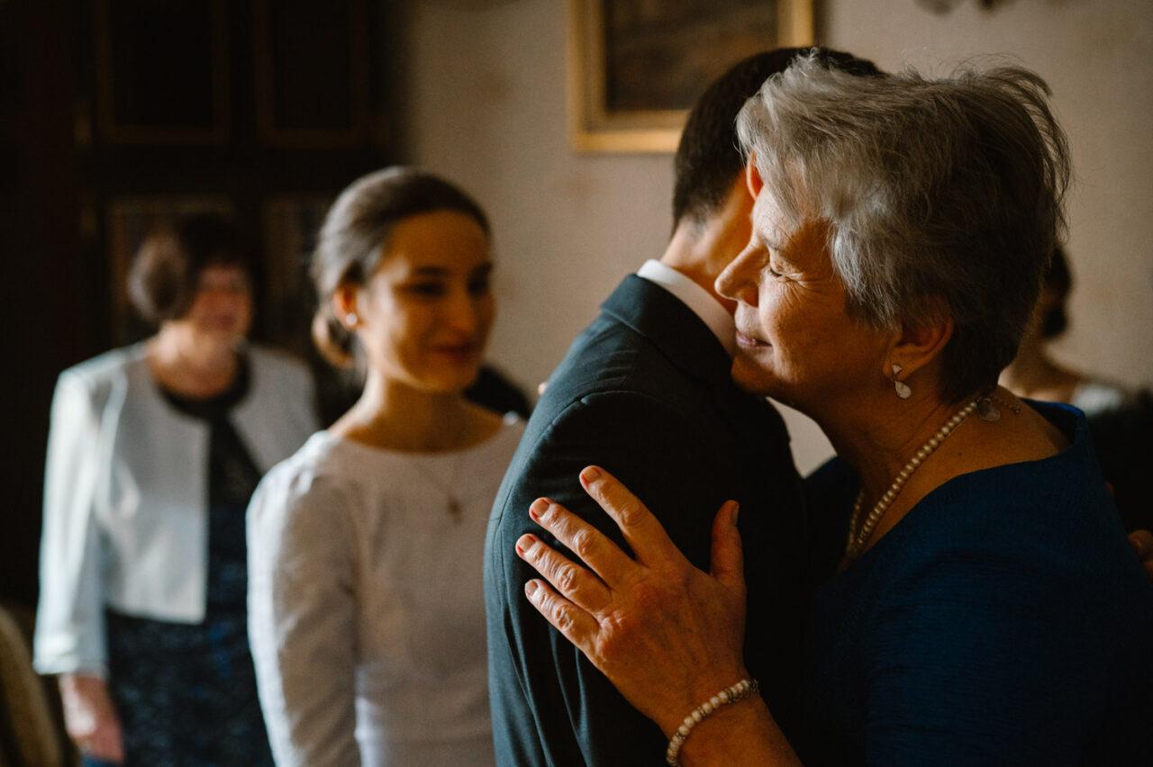 mama całuje pana młodego podczas błogosławieństwa
