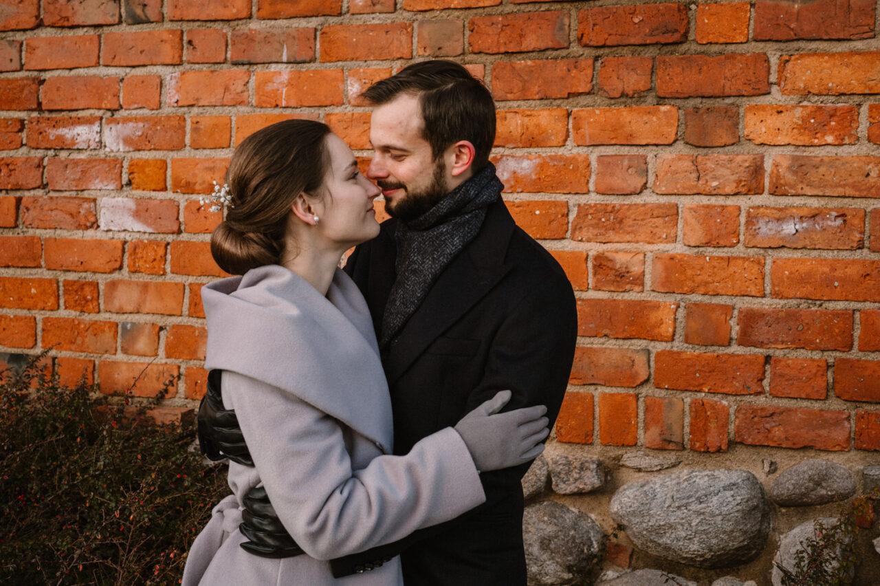 para młoda przytulająca się na tle ceglanej ściany