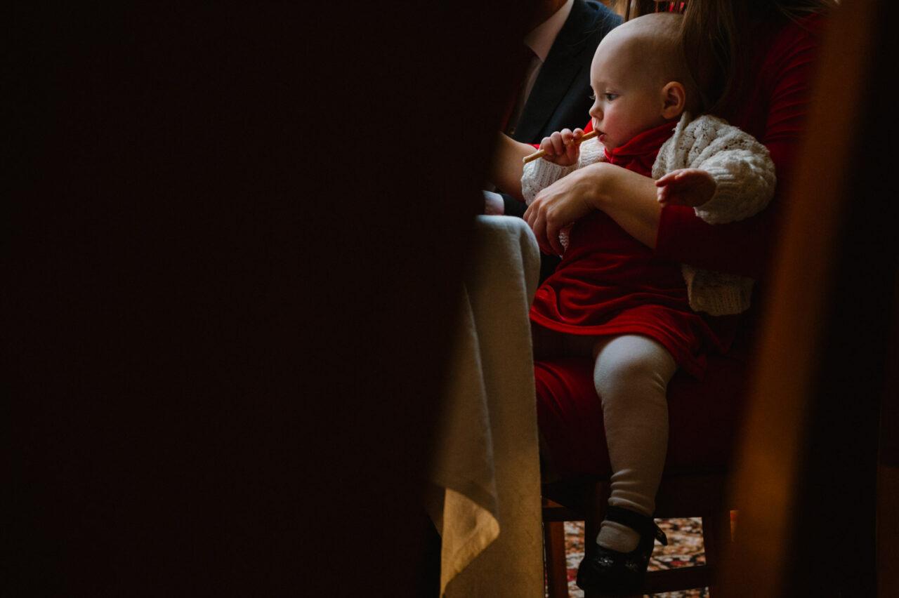 dziewczynka siedząca na nogach mamy