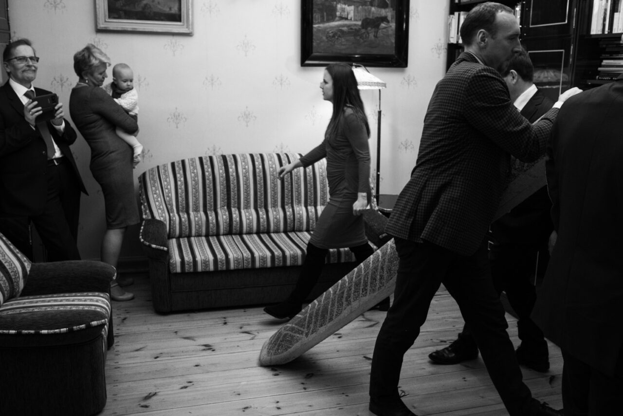 goście weselni sprzątają dywan z pokoju