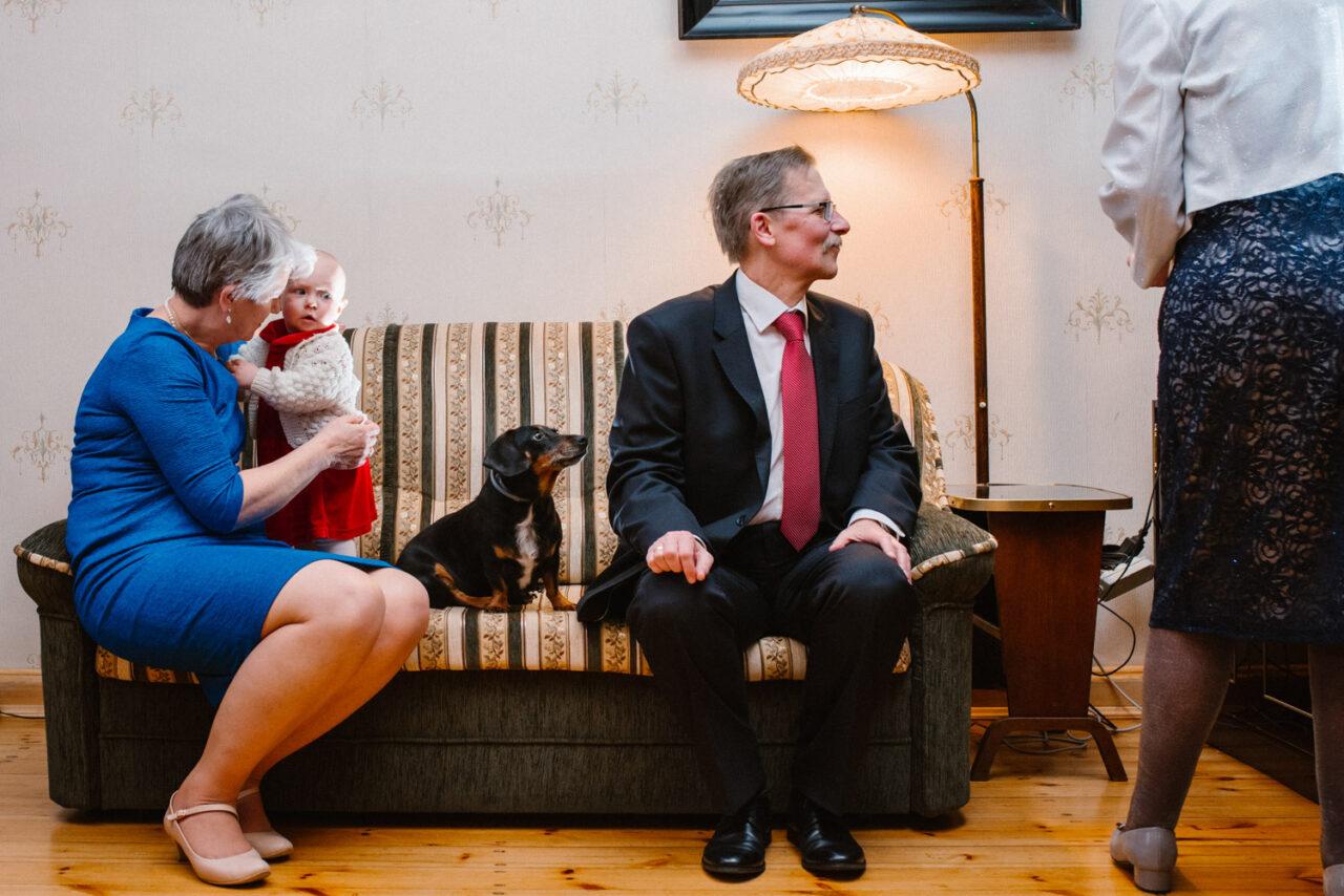 goście weselni siedzący na kanapie z psem i dzieckiem