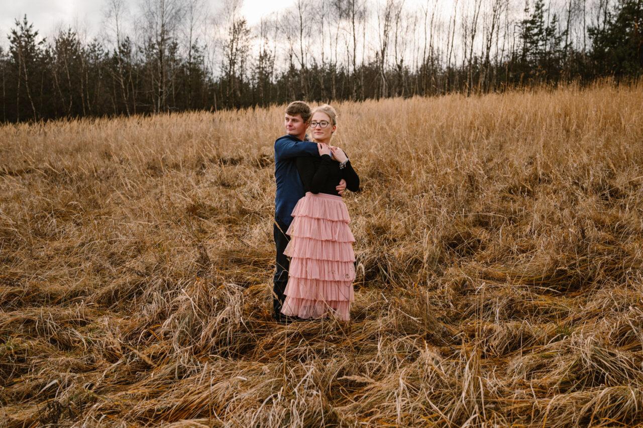 mężczyzna przytula kobietę na tle jesiennych traw