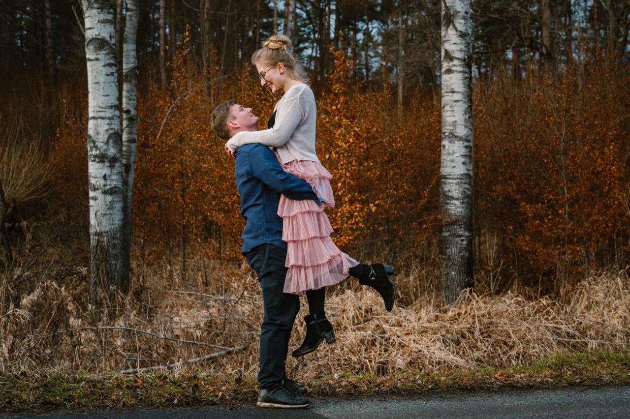 mężczyzna unosi ukochaną na tle jesiennego lasu