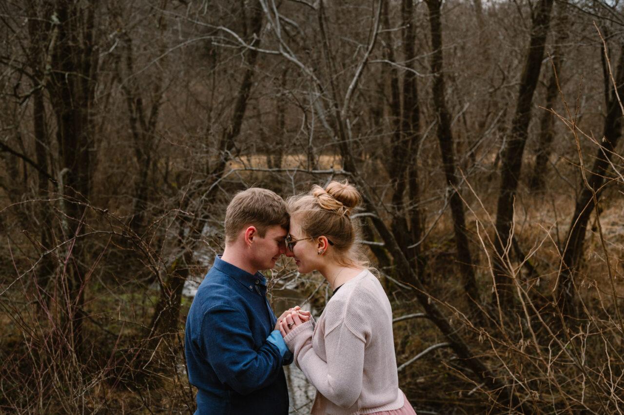 zakochani trzymają się za ręce na tle jesiennych drzew