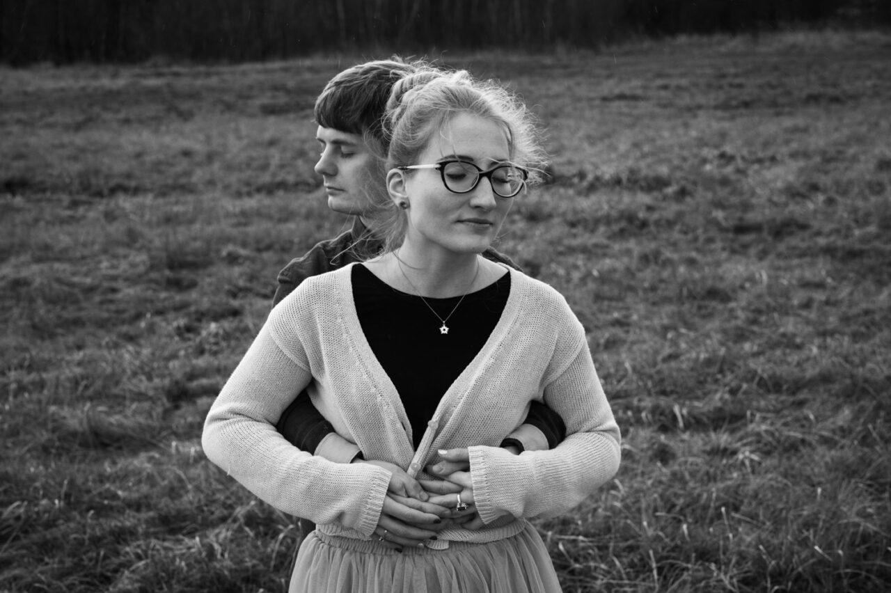 mężczyzna obejmuje kobietę na tle traw