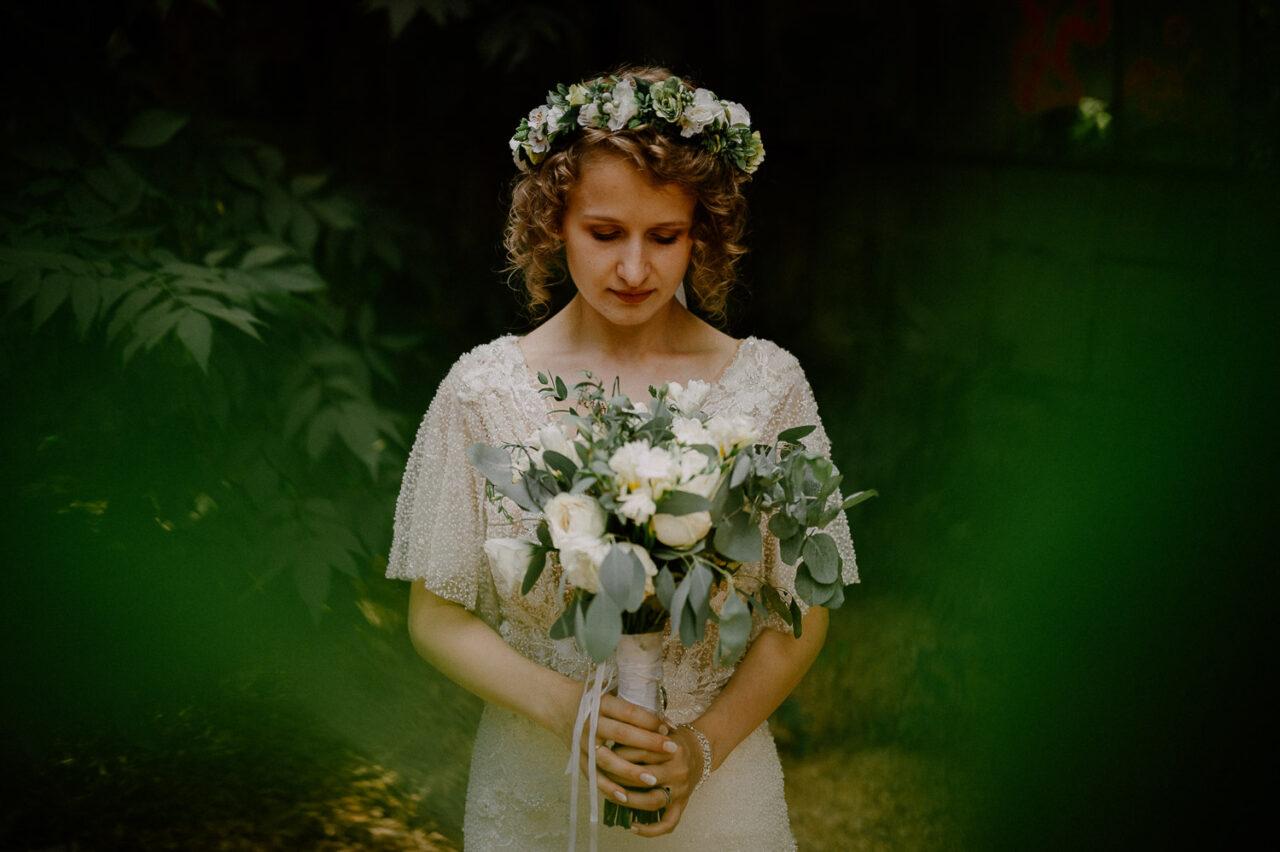 panna młoda we wianku trzyma bukiet ślubny