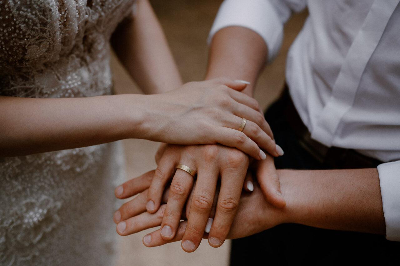 dłonie pary młodej z obrączkami i pierścionkiem zaręczynowym