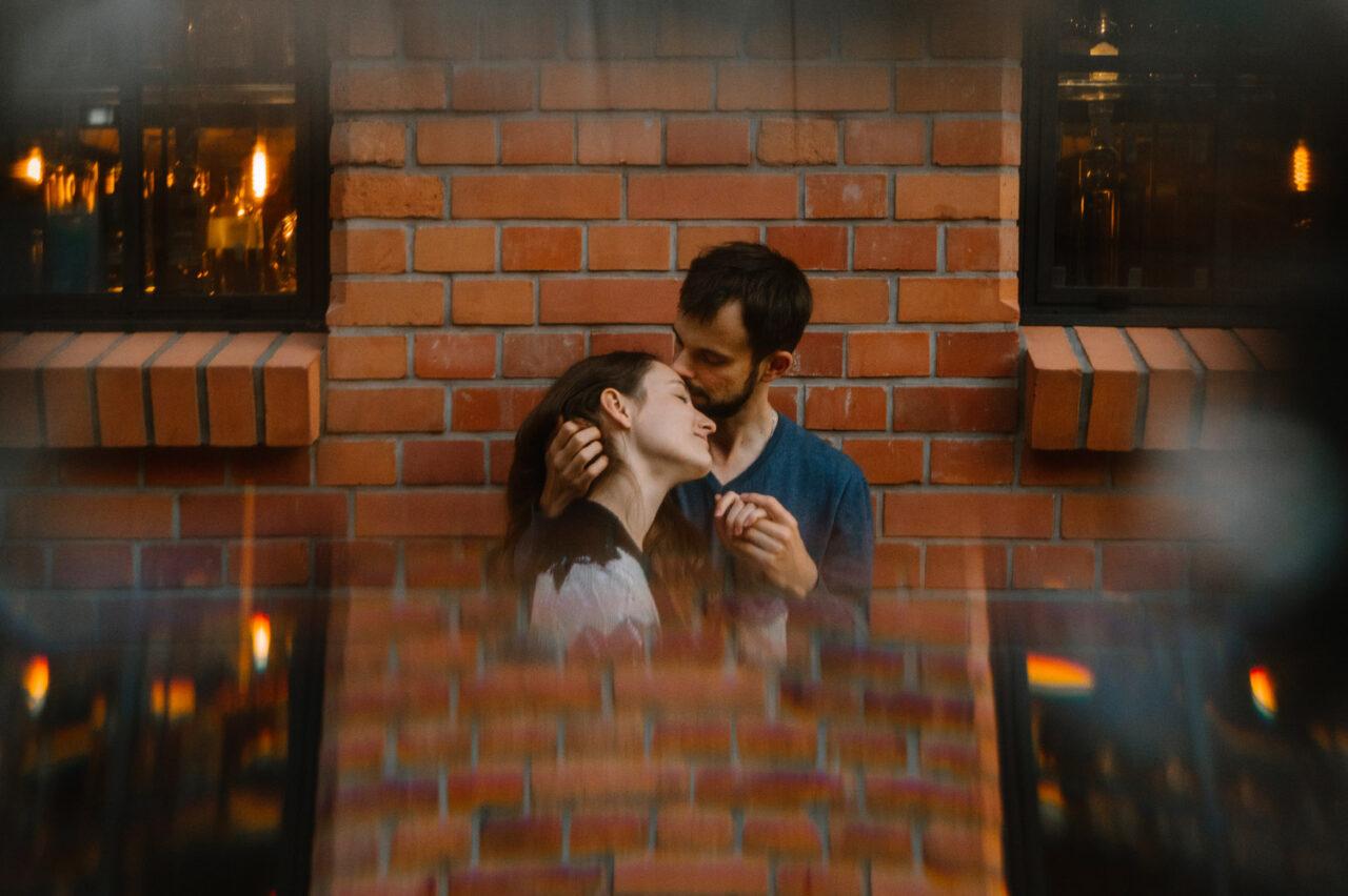 pocałunek zakochanych na tle ceglanej ściany