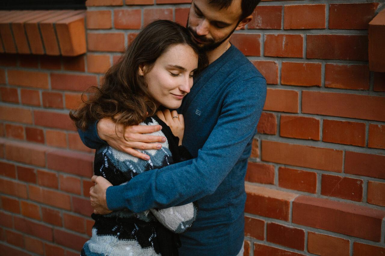 narzeczeni przytulająsię na tle ceglanej ściany