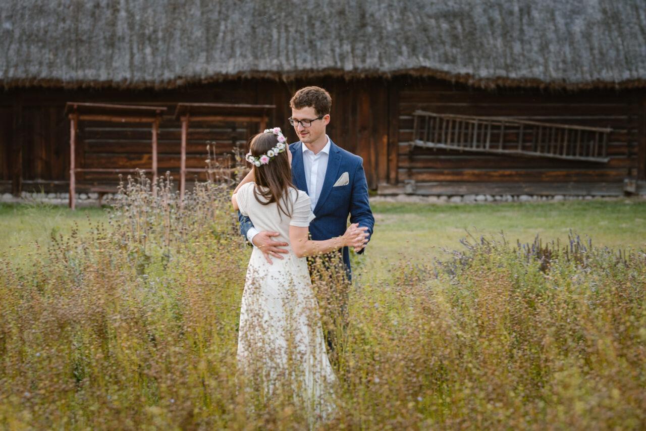 para młoda tańczy wśród ziół i roślin na tle stodoły