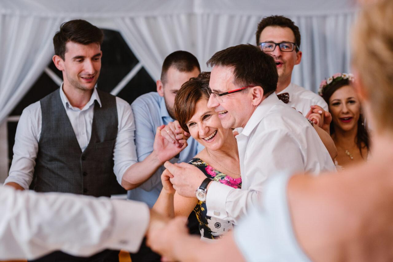 goście tańcząwokół rodziców pary młodej na weselu pod namiotem