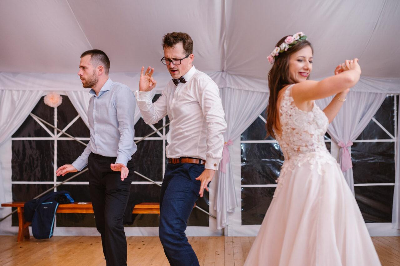 para młoda i goście tańczą na weselu rustykalnym
