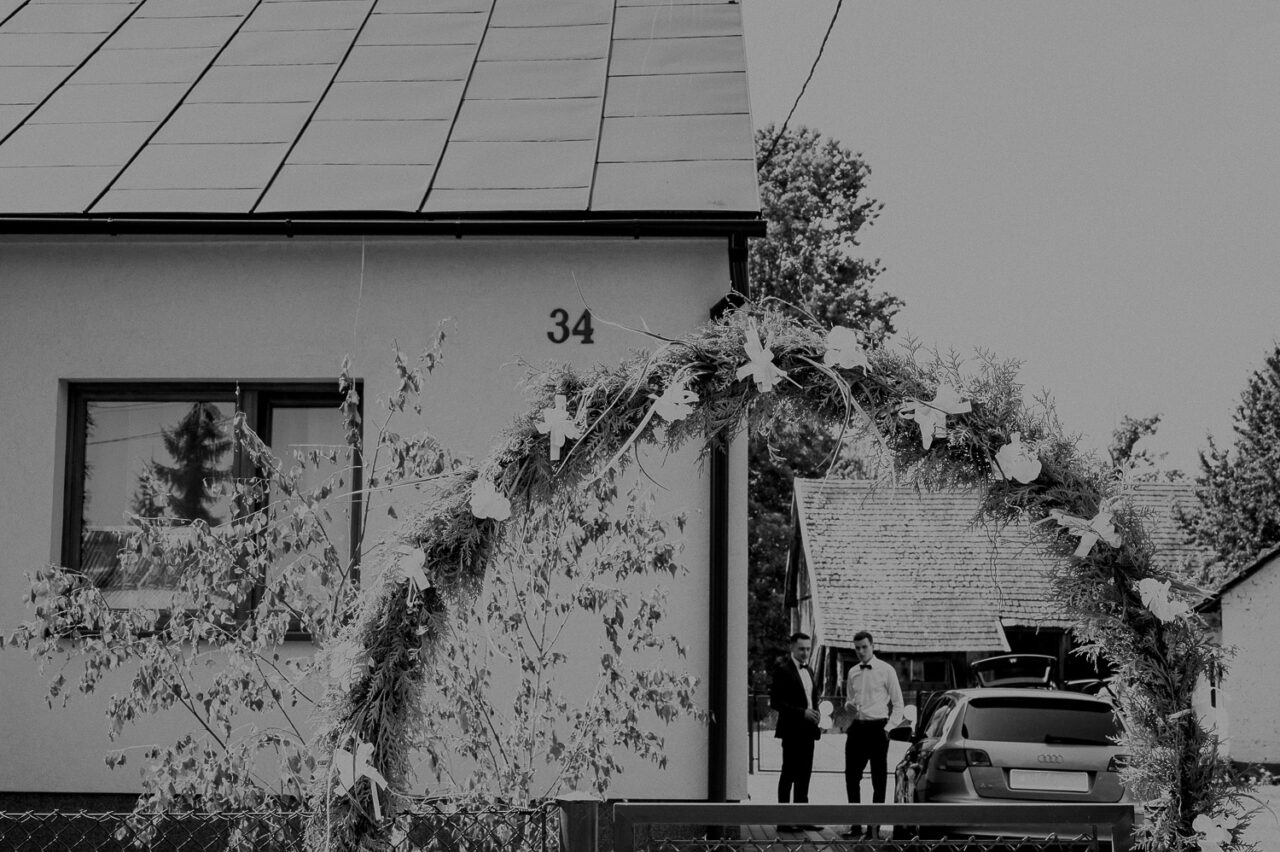 przed domem pana młodego - brama, auto i goście