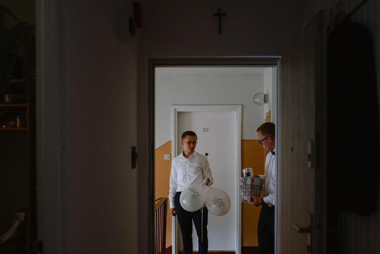 meżczyźni przypinają balony przed mieszkaniem panny młodej
