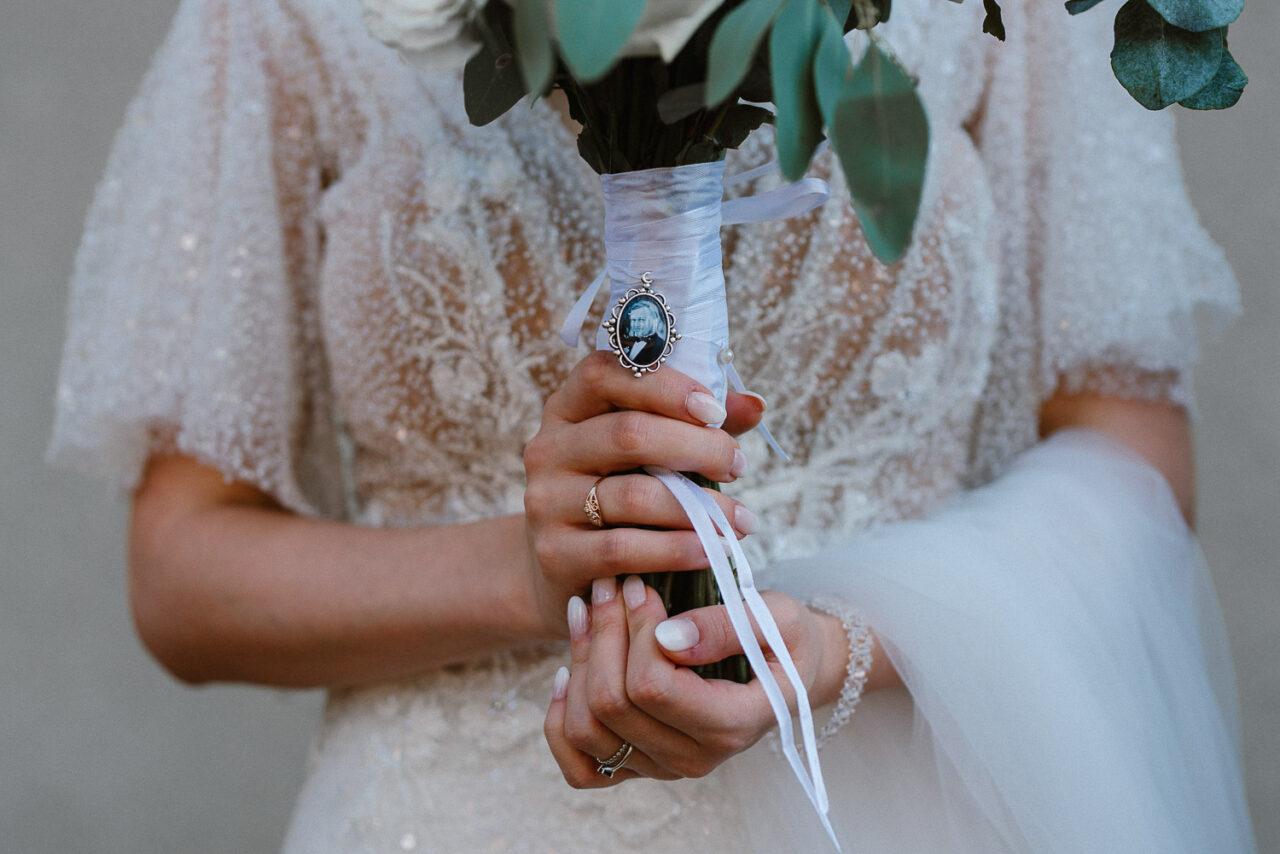 panna młoda trzymająca bukiet ślubny z medalionem
