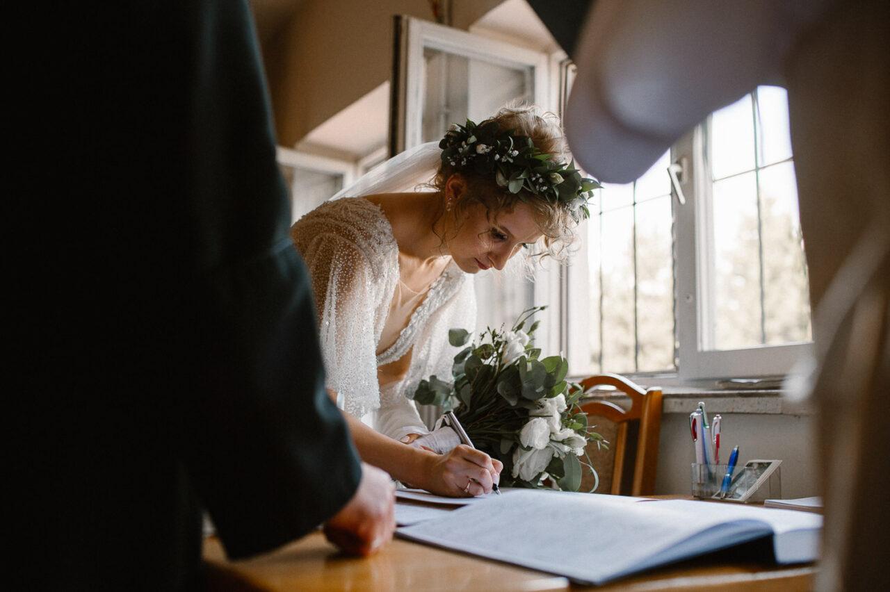 panna młoda podpisująca dokumenty ślubne w zakrystii