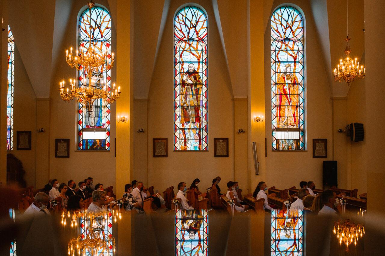 goście weselni na tle kościelnych witraży