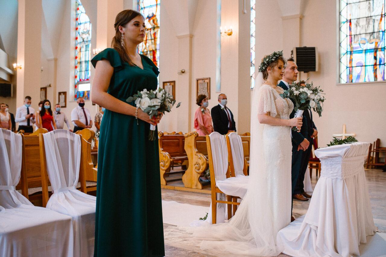 para młoda i druhna stoją w kościele