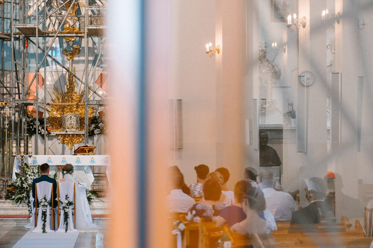 para młoda siedzi w kościele podczas ceremonii ślubnej