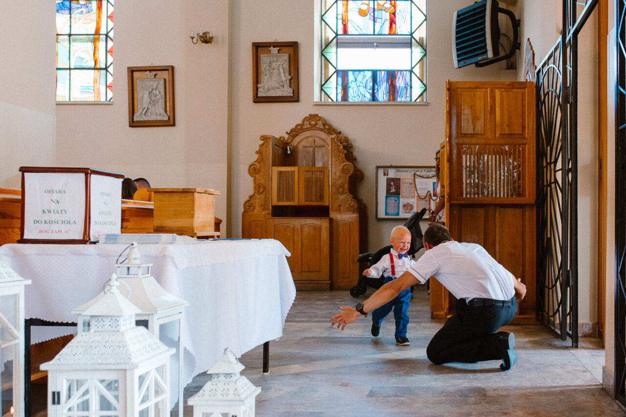 ojciec z otwartymi ramionami łapie dziecko biegające po kościele