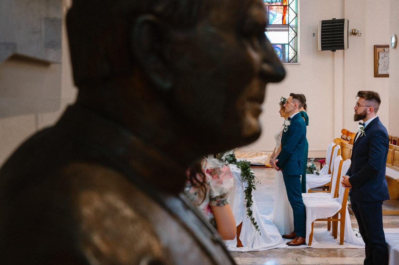 para młoda i świadek oraz portret Jana Pawła II w kościele