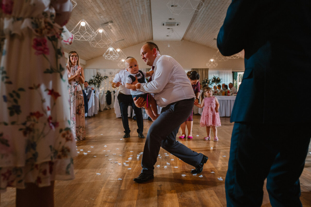 tato z synkiem tańczą na parkiecie weselnym wśród gości