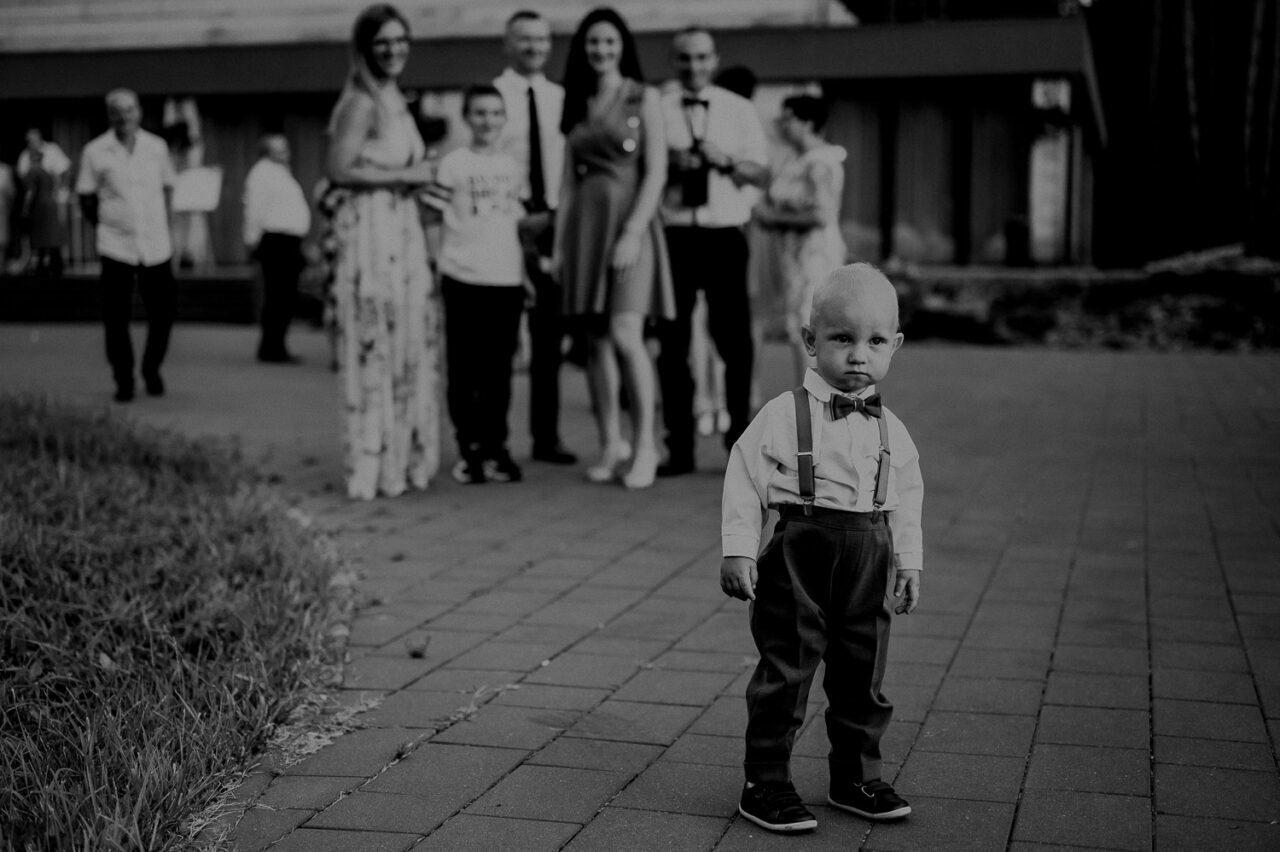 portret dziecka i gości weselnych przed leśną chatą