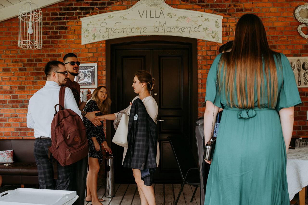 goście weselni witają się przed Villa Spełnione Marzenia