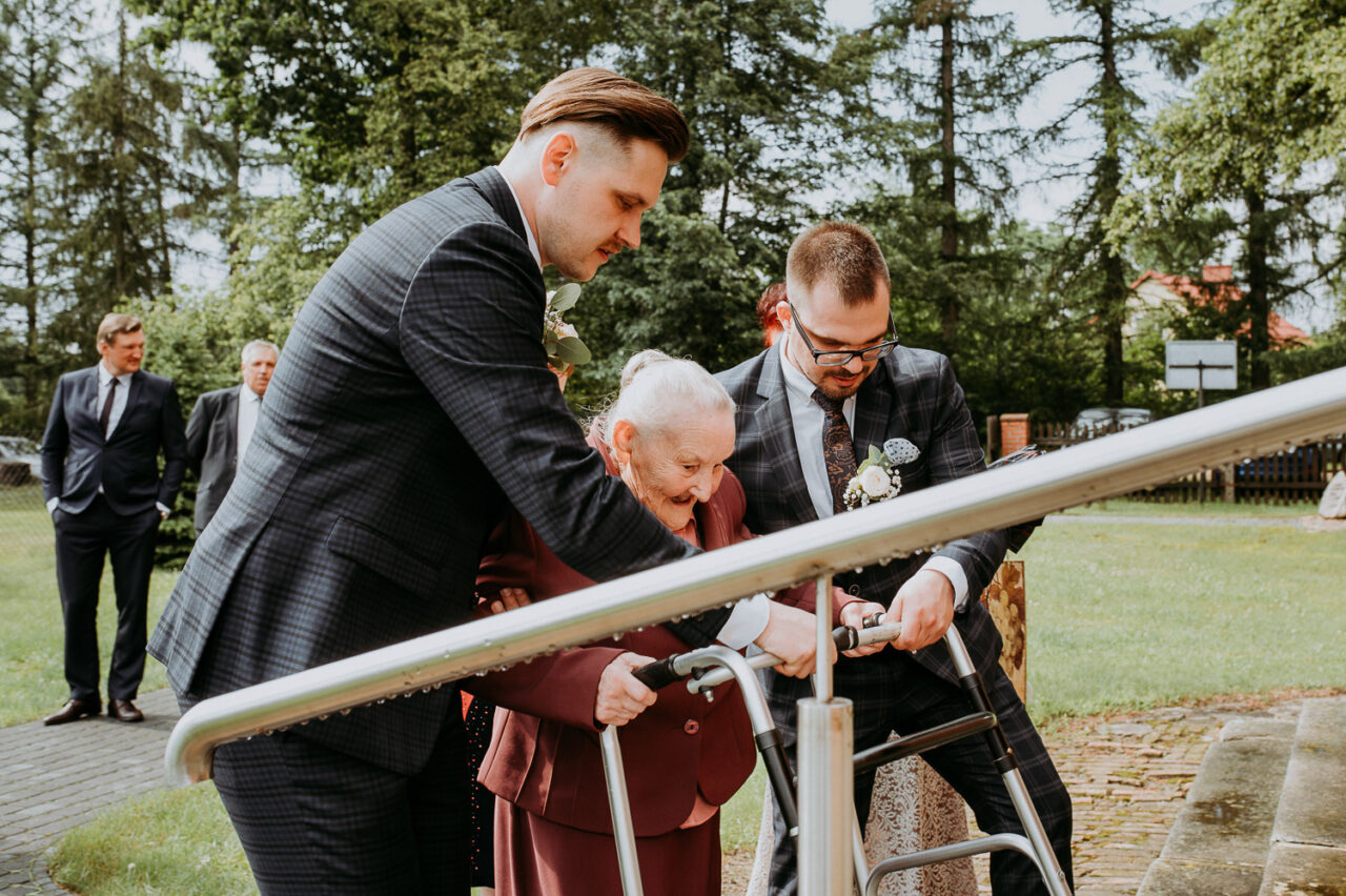 pan młody i drużba pomagają babci dotrzeć do kościoła