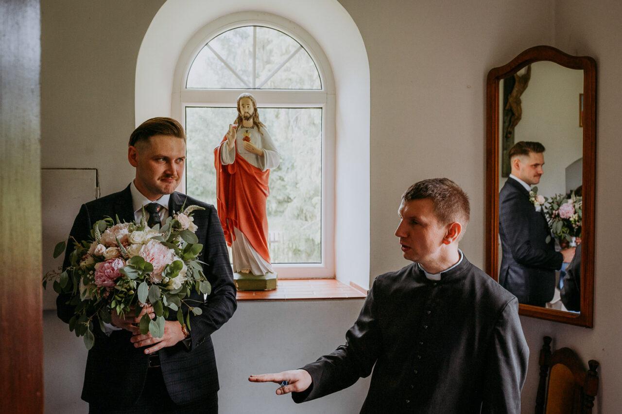 pan młody rozmawia z księdzem w zakrystii