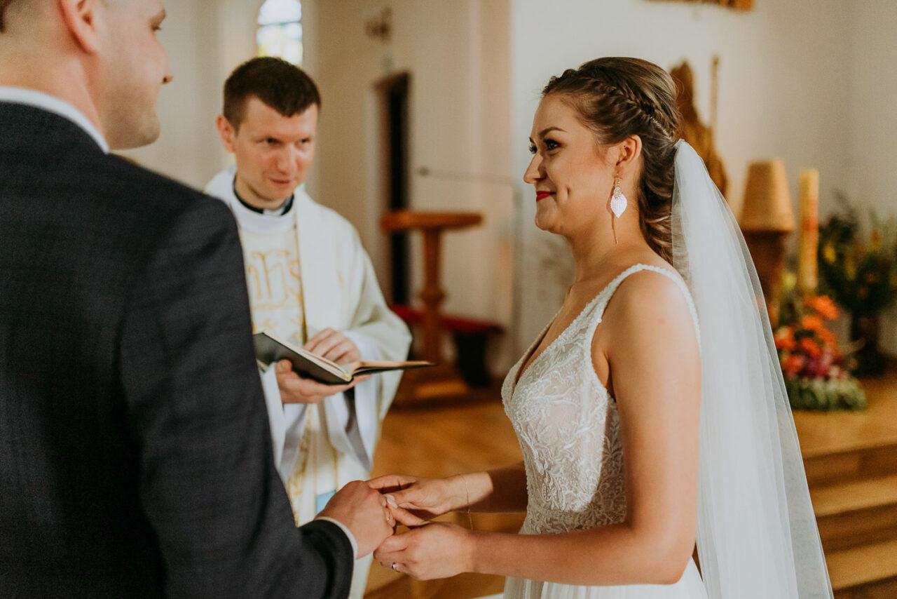 panna młoda zakłąda mężowi obrączkę ślubną w kościele
