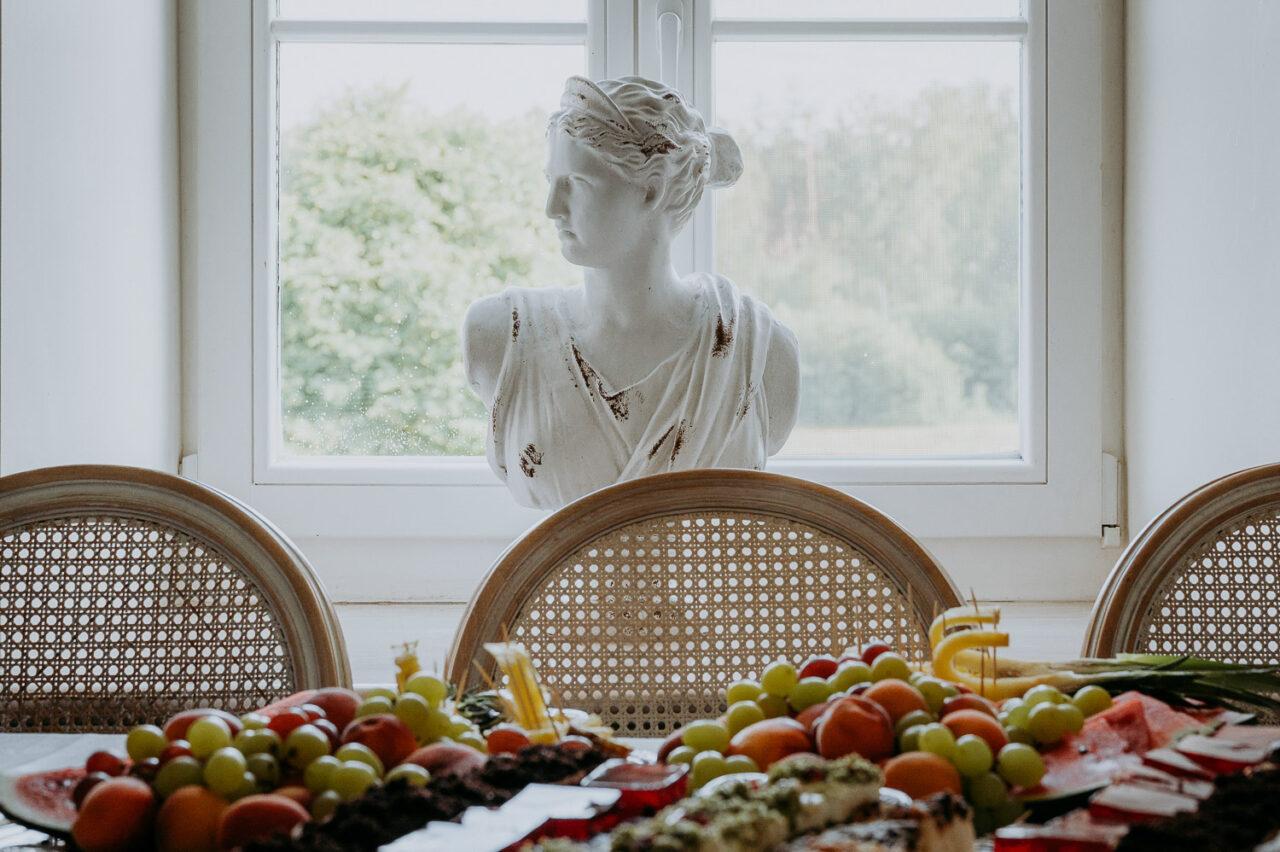 posągowe popiersie i stół słodkości