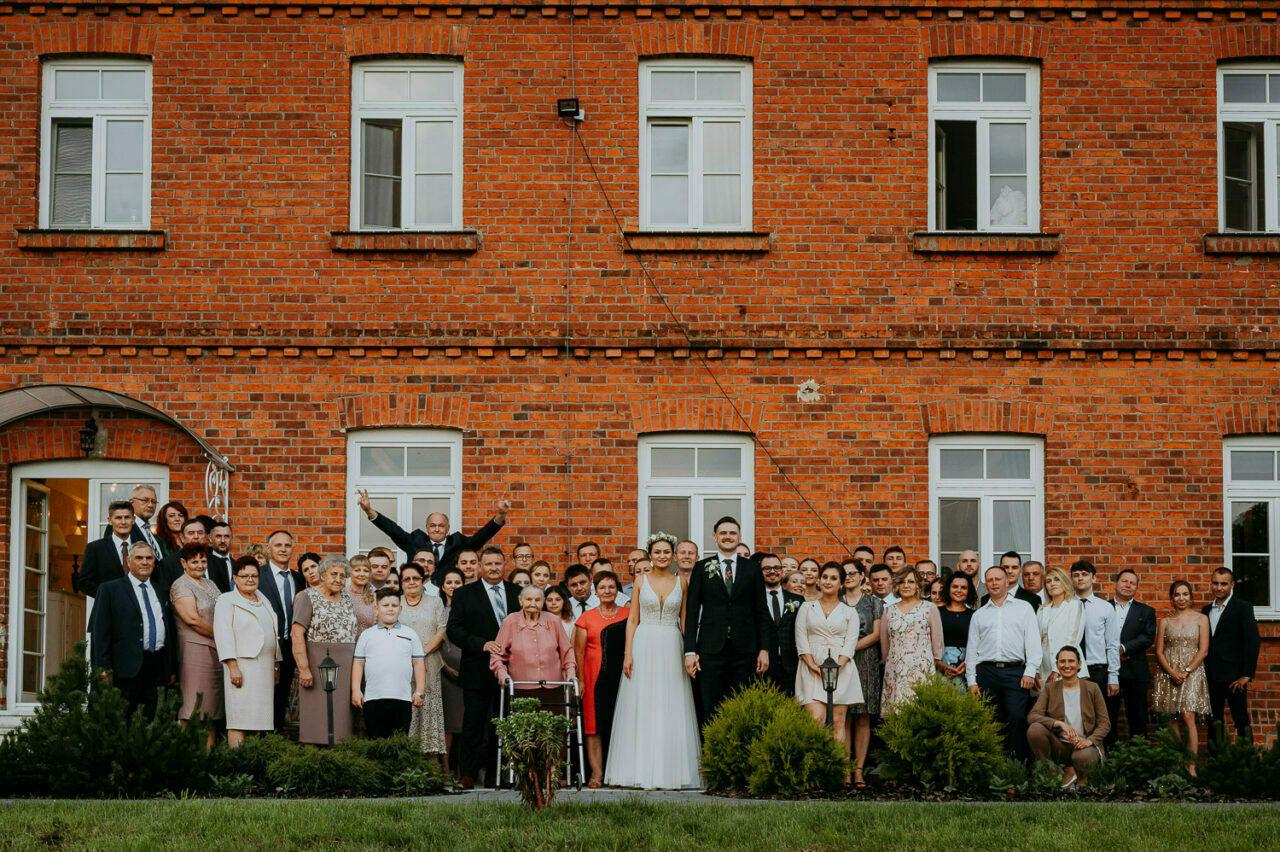 zdjęcie grupowe weselnych gości na tle ceglanej ściany