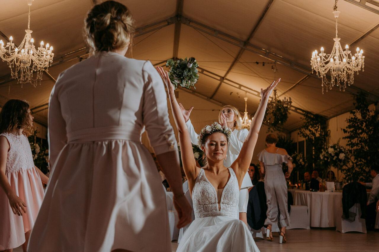 panna młoda rzuca bukietem na weselu w namiocie