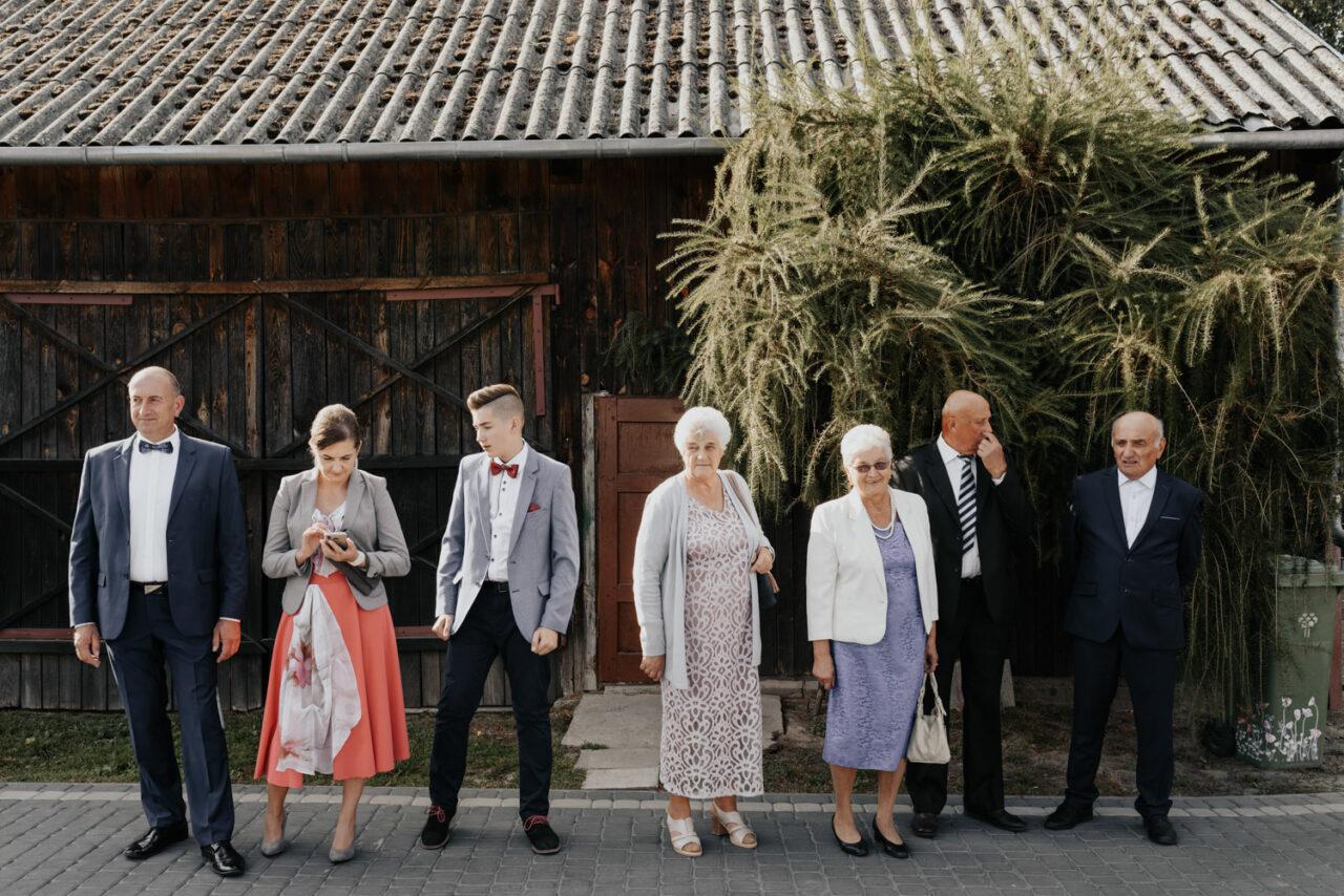 weselni goście czekający przy stodole
