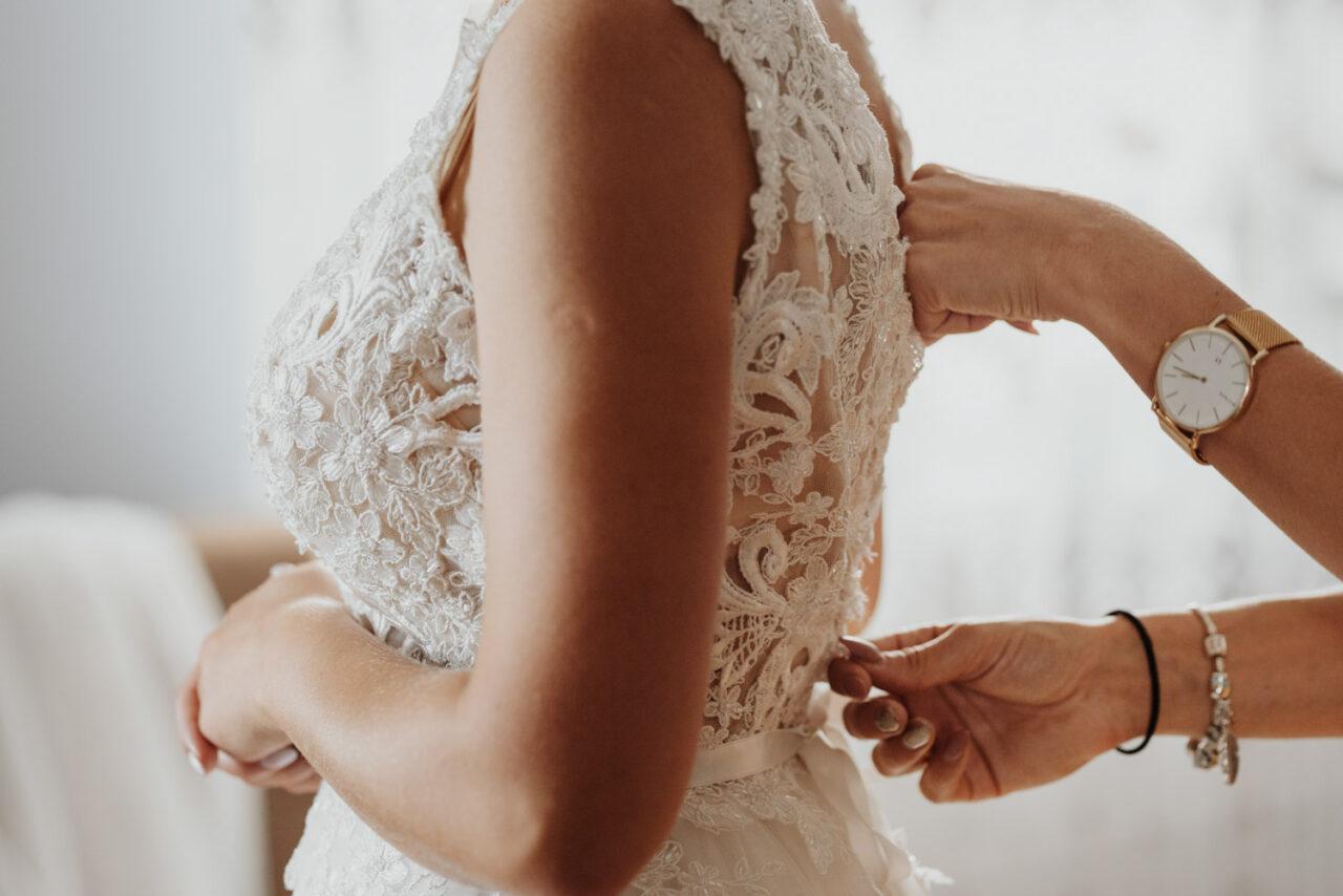 dłonie panny młodej i druhny zapinającej suknię