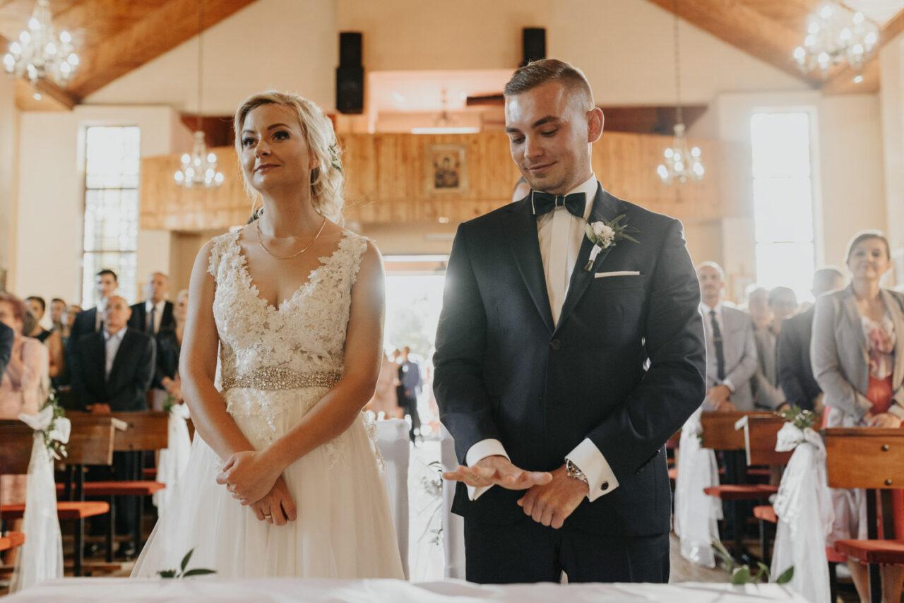 para młoda ogląda obrączki ślubne w kościele
