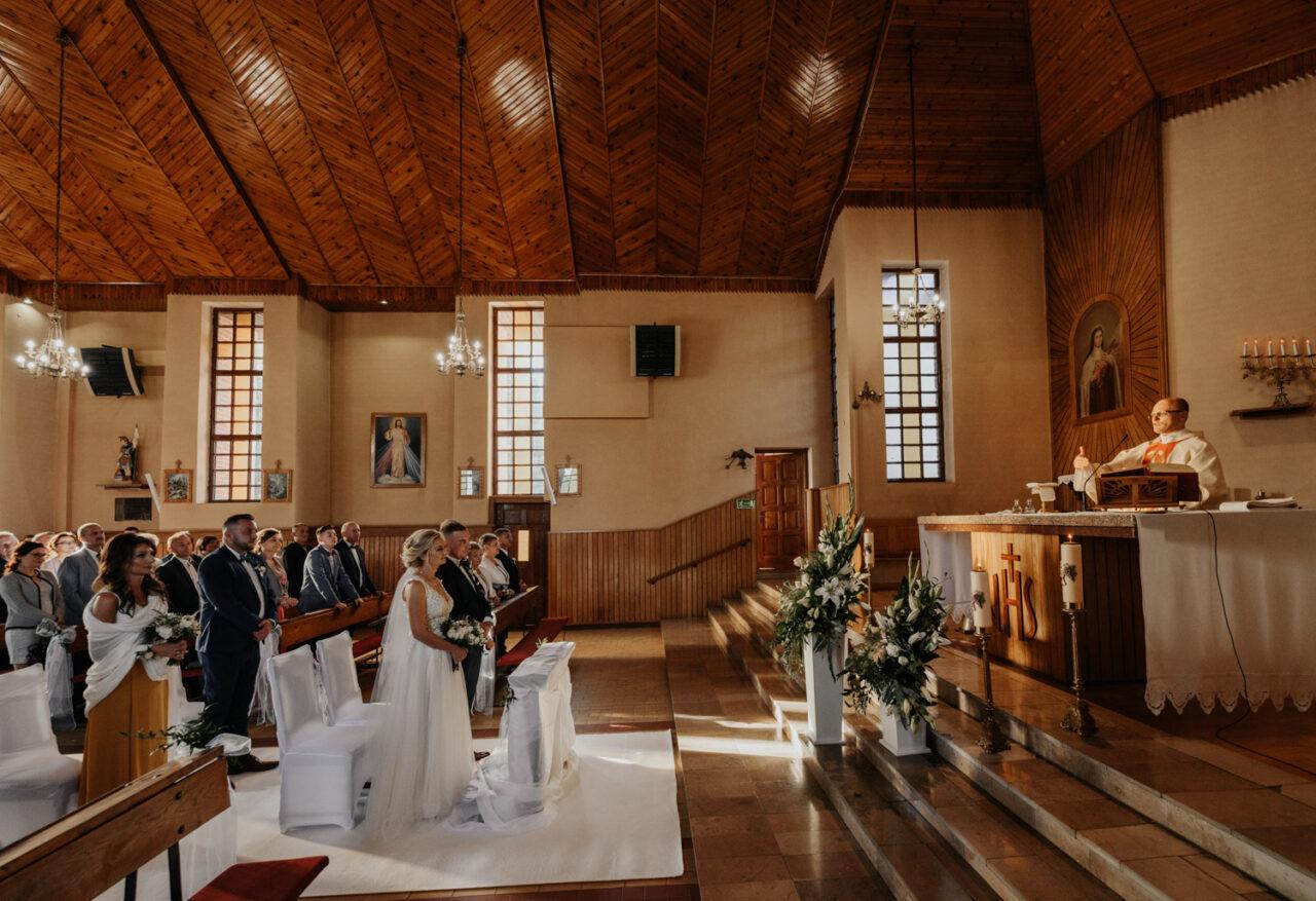 ksiądz błogosławi młodej parze w kościele