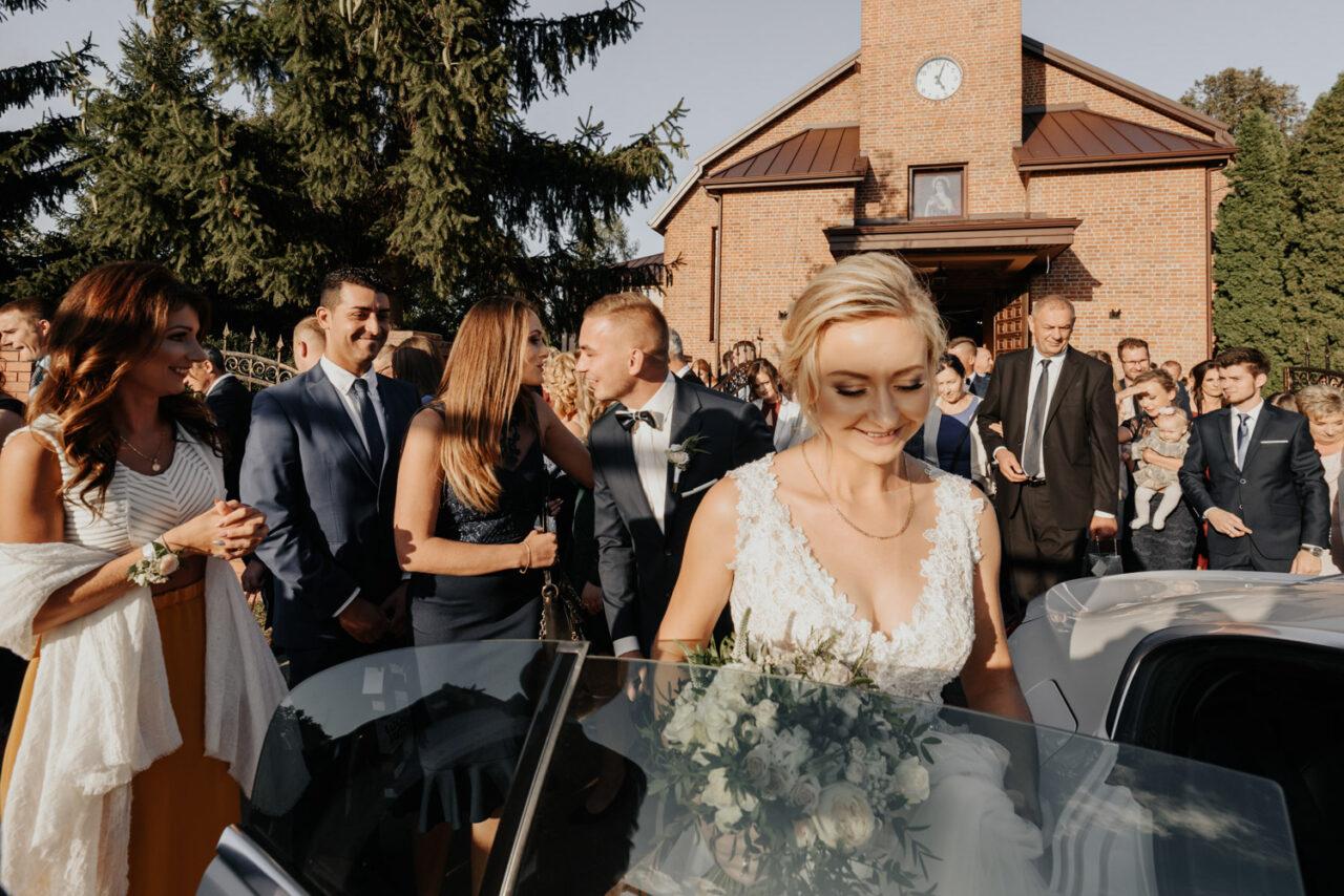 panna młoda wsiada do auta na tle gości weselnych