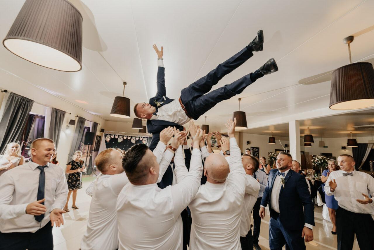 panowie podrzucają pana młodego podczas wesela